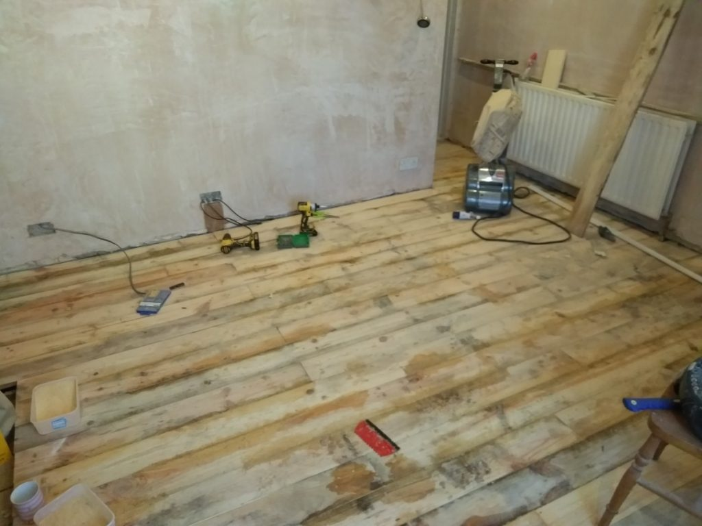 Gap In Floorboards Filling With Resin And Sawdust